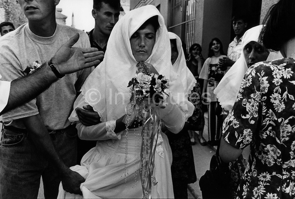 """Wedding in Muslim East Mostar as life returns to normal after the Dayton Peace Accords.  It wasdestroyed by systemic bombardment from Croat guns during the Croat Muslim War, when the Croats endeavored to """" cleanse"""" the town of non Croats. Mostar, Bosnia and Herzegovina."""