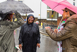 London, August 31st 2015. Labour mayoral candidate Diane Abbot chates with two women waiting for the procession to begin as revellers ignore the inclement weather to enjoy day two of the Notting Hill Carnival.
