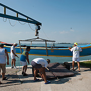 """VENICE, ITALY - SEPTEMBER 04:  Members of the Voga Veneta Lido rowing club launch a """"Caorlina"""" a traditional Venetian boat using a boat crane ahead of Sunday Historic Regata on September 4, 2010 in Venice, Italy. The Historic Regata is the most exciting rowing race on the Gran Canal for the locals and one of the most spectacular ***Agreed Fee's Apply To All Image Use***.Marco Secchi /Xianpix. tel +44 (0) 207 1939846. e-mail ms@msecchi.com .www.marcosecchi.com"""