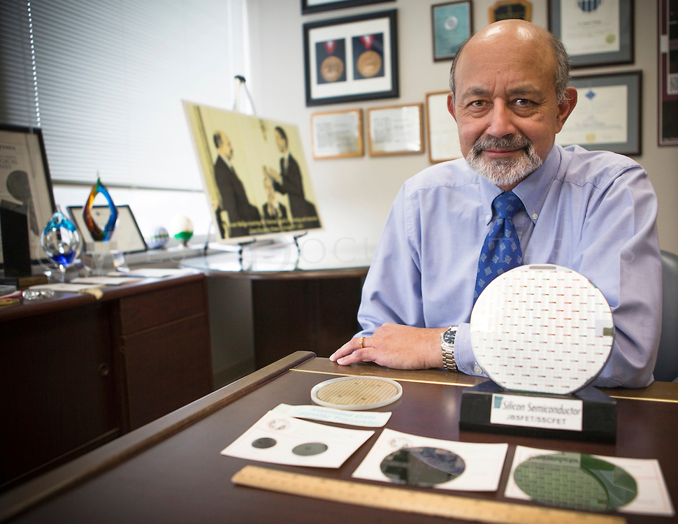 B. Jayant Baliga, NCSU Distinguished University Professor and recognized expert on power semiconductor devices, poses with a variety of semiconductors from the last 30 years.