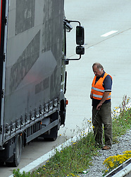 © Licensed to London News Pictures. 28/07/2015<br /> Lorry driver urinating in the middle of the M20 while stuck in operation stack.<br /> <br /> Operation stack lorries between J8 and J9 for Ashford on the M20. <br /> Operation stack is back on the M20 in Kent.<br /> Just days after Operation Stack was taken off the M20, it was brought back in the early hours of this morning.<br /> The authorities are blaming a heavy volume of traffic heading towards the Port of Dover and Eurotunnel and the continued disruption in Calais.<br /> The coast-bound carriageway between junctions 8 and 9 is closed to allow lorries to park, but the slip roads at junctions 9, 10 and 12 and 13 have also been shut. <br /> <br /> (Byline:Grant Falvey/LNP)