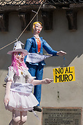 """An effigy of U.S. President Donald Trump hangs in the Plaza Allende with other paper dolls in preparation for the Burning of Judas Easter-time ritual marking the end of Holy Week April 1, 2018 in San Miguel de Allende, Mexico. While the tradition includes burning a paper effigy of Judas a recent popular addition has been paper doll caricatures of Donald Trump across Mexico. The doll is holding a sign saying """"No Wall"""" in reference to the Trump border wall."""