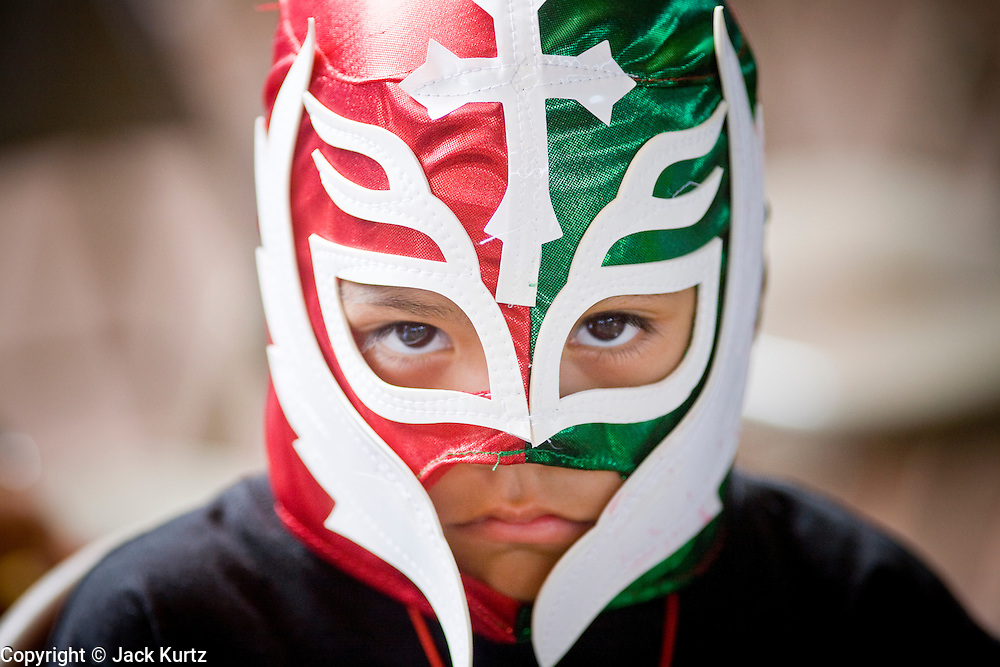 July 13, 2008 -- PHOENIX, AZ: Children wearing Lucha Libre masks at a Lucha Libre show at El Gran Mercado in Phoenix. Lucha Libre is Mexican style wrestling. There are heros (Tecnicos) and villians (Rudos). The masks are popular as children's gifts and tourist mementos. As the size of the Mexican community in the Phoenix area has grown, attendance at the Lucha Libre shows has increased. Lucha Libre differs from American style entertainment wrestling in several ways, but principally the wrestlers are more acrobatic and rely less on body slams than American wrestling. The shows, which used to be held only periodically, are now held every week at El Gran Mercado, a flea market and swap meet that caters mostly to the Mexican community in Phoenix.   Photo by Jack Kurtz / ZUMA Press