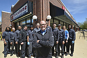 Employees at the Firestone Complete Auto Care facility in Clayton, MO, on Friday, April 12, 2019 in St. Louis. From left: Bryan Hicks (technician), Jimmy Hynes (technician), Jaky Ranaivoarisoa (technician), Brad Clutter (MVS), Q Valiant-Channel (technician), Steve Hamm (MTS), Chris Crowell (Managing Partner), Darvin Wallace (maintenance technician), Nick Waganer (technician), Sewon An (technician), Jen Notestine (sales representative), and Keith Tabor (technician).<br /> (Tim Vizer/AP Images for Bridgestone Retail Operations)
