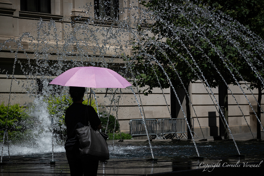 A lady is prepared in case the fountain in front of the Metropolitan Museum goes rogue.