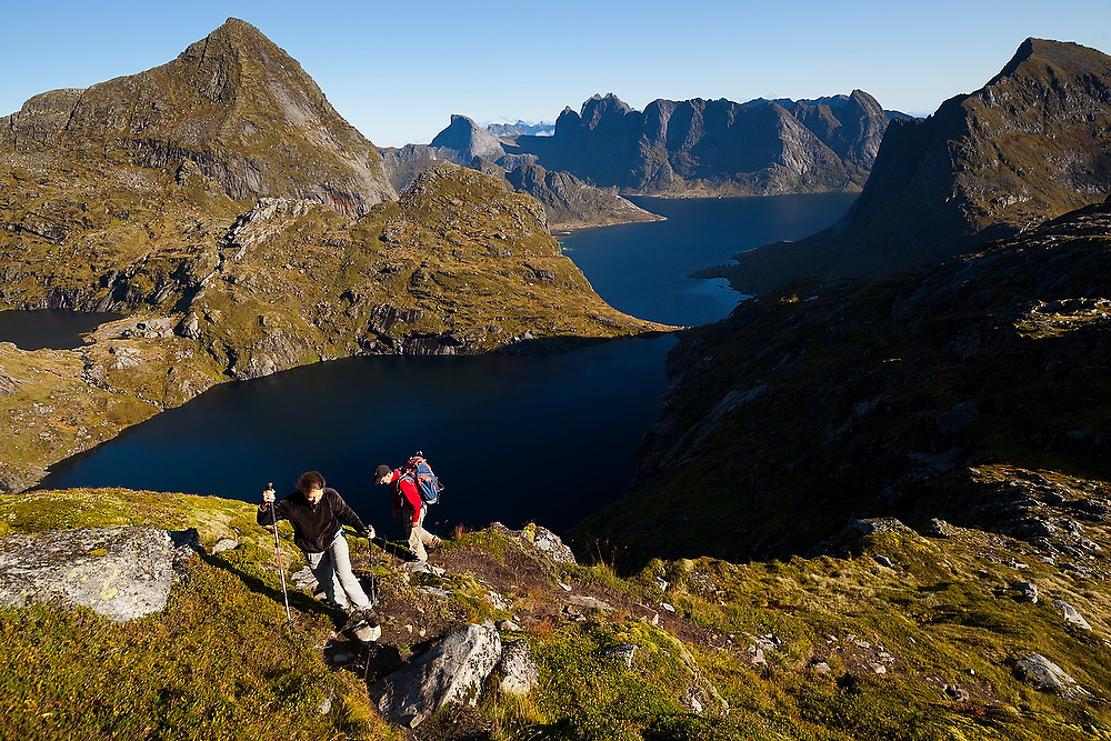Liana (left) and Parmenter Welty hike towards the summit of Hermannsdalstinden, the highest mountain in western Lofoten Islands, Norway.