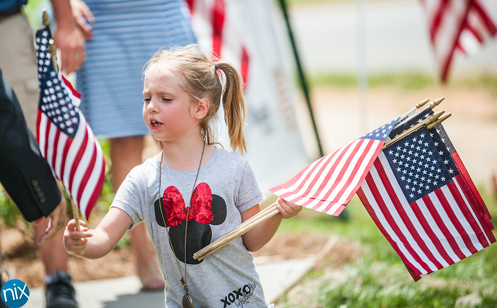 Zoe Allercamp, 5, hands out American flags prior a ceremony welcoming Sgt. Andrew Mullee to his new home in Kannapolis Thursday afternoon. Mullee and his family received a four-bedroom, handicap-accessible home built for by HelpingaHero.org and the Patriot Charities. The homesite was donated by Kellswater Bridge. While deployed to Afghanistan, Mullee was seriously injured by a IED explosion on May 12, 2012. As a result he lost his right leg at the knee and part of his left calf, among other injuries.