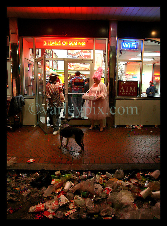 Feb 28th, 2006. New Orleans, Louisiana. Mardi Gras Day, Fat Tuesday, Bourbon Street. The party is over. Trash piled up in the street after Midnight, early in the morning of Ash Wednesday. Dressed up in costume, a 'lady' stands with a dog outside a late night eatery.