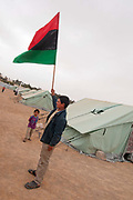 Tunisia 2011. Remada camp for refugees from Libya. After Friday prayers refugees (mostly mothers and children) held a demonstration around the camp. Young boy holding a pre Gaddafi flag