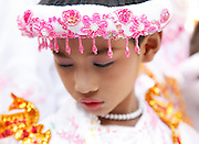Young boy dressed as girl for Buddhist initiation ceremony. Bagan, Myanmar.