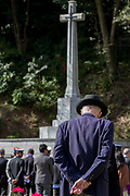 An old man watches dignitaries and laying wreaths of poppies at the Cross of Sacrifice Remembrance Sunday ceremony at the Hodogaya, Commonwealth War Graves Cemetery in Hodogaya, Yokohama, Kanagawa, Japan. Sunday November 12th 2017. The Hodagaya Cemetery holds the remains of more than 1500 servicemen and women, from the Commonwealth but also from Holland and the United States, who died as prisoners of war or during the Allied occupation of Japan. Each year officials from the British and Commonwealth embassies, the British Legion and the British Chamber of Commerce honour the dead at a ceremony in this beautiful cemetery.