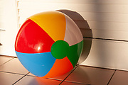 Multicolored beach ball sitting on a outdoor tile counter lit with late afternoon sunlight