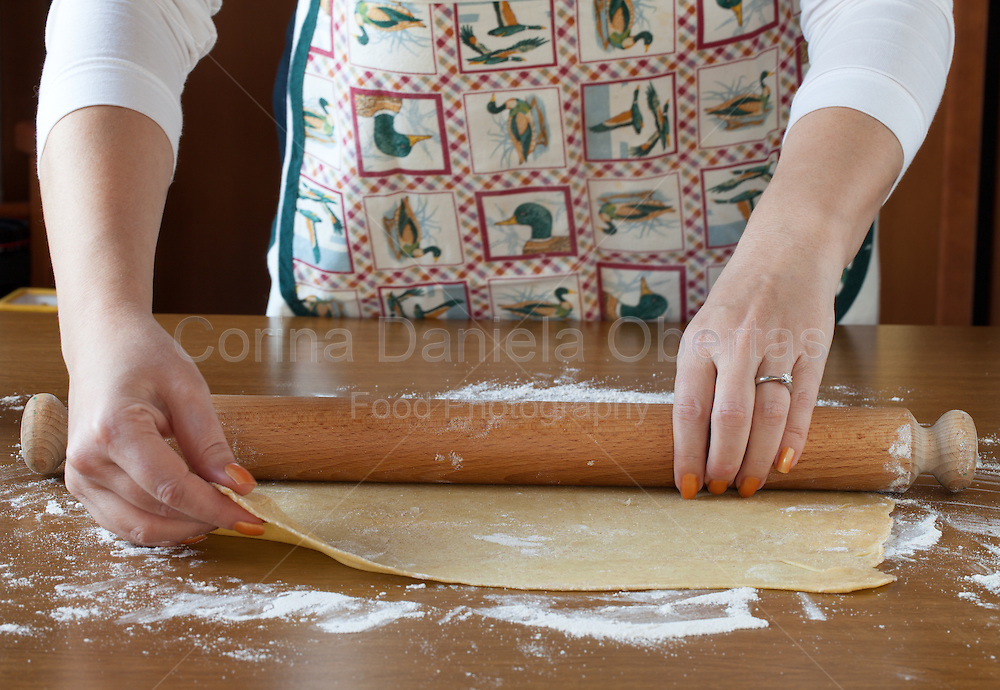 Woman rolling out homemade pasta sheet on wooden table.