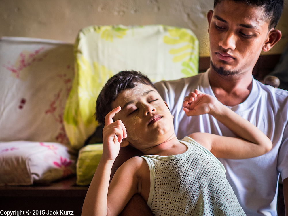 02 JUNE 2015 - KULAI, JOHORE, MALAYSIA: A Rohingya man takes care of MOHAMMAD SHIDE, 6 year old, Rohingya refugee. The man helps take care of the boy when his mother is at work. The child was born healthy but developed symptoms similar to polio before they came to Malaysia from Myanmar. Now his mother can't afford a proper medical diagnosis and his condition is worsening. He is now blind and losing control of his muscular system. His mother doesn't know what is wrong with him but earns less than $6 US per day selling used books on the street and can't afford medical care. The UN says the Rohingya, a Muslim minority in western Myanmar, are the most persecuted ethnic minority in the world. The government of Myanmar insists the Rohingya are illegal immigrants from Bangladesh and has refused to grant them citizenship. Most of the Rohingya in Myanmar have been confined to Internal Displaced Persons camp in Rakhine state, bordering Bangladesh. Thousands of Rohingya have fled Myanmar and settled in Malaysia. Most fled on small fishing trawlers. There are about 1,500 Rohingya in the town of Kulai, in the Malaysian state of Johore. Only about 500 of them have been granted official refugee status by the UN High Commissioner for Refugees. The rest live under the radar, relying on gifts from their community and taking menial jobs to make ends meet. They face harassment from Malaysian police who, the Rohingya say, extort bribes from them.     PHOTO BY JACK KURTZ