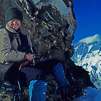 An early trekker rests atop 5780m Amphu Laptsa Pass between the Hongu Basin and Imja Valley in Nepal's Khumbu Region of the Himalaya. Lhotse Peak towers in the background.  (1980)
