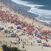 Sunbathers on Ipanema Beach, Rio de Janeiro, looking towards Arpoador point, Rio de Janeiro,  Brazil. 29th July 2010. Photo Tim Clayton...