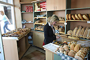 Greece, Macedonia, Castoria; Woman buying bread in a local bakery