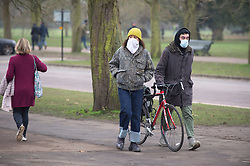© Licensed to London News Pictures 10/01/2021.         Greenwich, UK. Two people wearing face coverings. People out and about in Greenwich park, London this Sunday afternoon during a third national Covid lockdown. The Home Secretary Priti Patel has said police officers will take action where people are breaking Covid rules. Photo credit:Grant Falvey/LNP