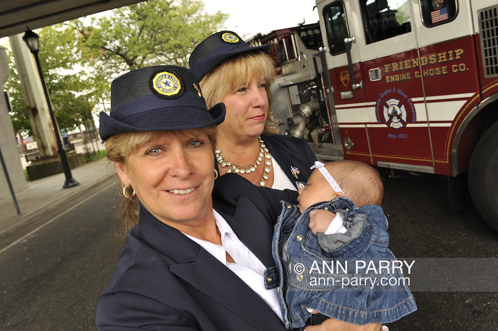 L-R, Debra Bernhardt (holding baby) and Claudia Borecky, Auxiliary members of Merrick Post 1282 American Legion. On 10th anniversary of 9/11, Merrick Fire Department ceremony at Merrick Railroad Station, with relatives of those lost during 9/11 attack in NYC, firefiighters, Auxiliary members of Merrick Post 1282 of American Legion, with Robbie Rosen singing National Anthem, Brownie Troop 2272 which keeps the Merrick Sta. Memorial Plaza clean, on September 11, 2011, in Merrick, New York, USA.