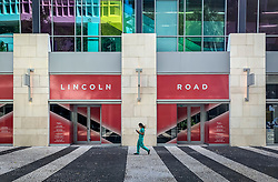A lone pedestrian walks along the deserted Lincoln Road Mall, which is usually crowded with tourists and local residents, on March 18,2020.