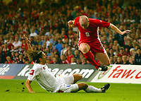 Photograph: Scott Heavey.<br />Euro 2004 Group 9 Qualifying match.<br />Wales v Serbia and Montenegro. 11/10/2003.<br />John Hartson is tackled by Goran Gavrancic