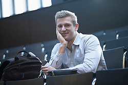 Portrait of a college student sitting in lecture hall and listening lecture, Freiburg im Breisgau, Baden-Wuerttemberg, Germany
