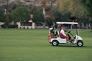 women driving golf cart on golf course