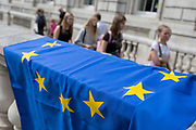 On the day that British Prime Minister Boris Johnson sought to have Parliament suspended by Queen Elizabeth, days after MPs return to work in September - and only a few weeks before the Brexit deadline, tourists walk past pro-EU Remain voters protest outside the Cabinet Office where daily Brexit contingency planning meetings take place, on 28th August 2019, in Whitehall, Westminster, London, England.