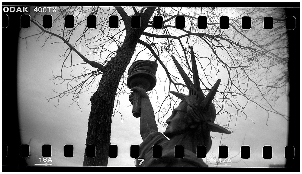 """A miniature Statue of Liberty is seen on the front lawn of """"Peace House"""" in Crawford, Texas, December 13, 2008. Bush moved to the small Texas town, population 705, in 1999 during his run for the presidency in 2000. The effect of the image was achieved by shooting 35mm black and white film in a medium format camera thereby exposing the entire negative including the sprocket holes of the film. REUTERS/Jim Young"""