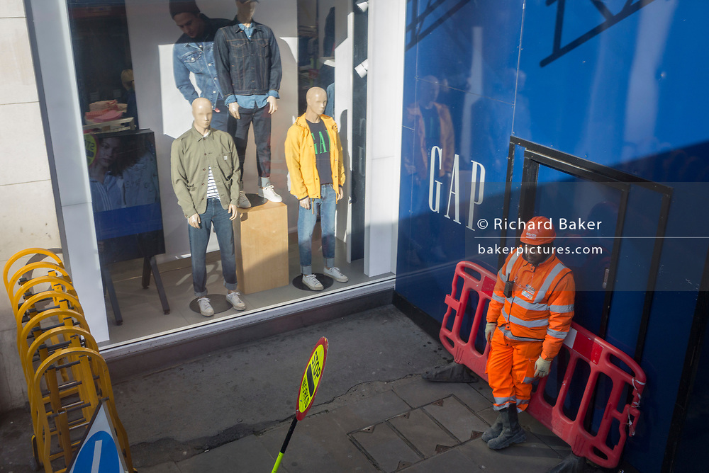 A construction worker leans against a barrier in front of the entrance to a project, and alongside the window display of clothing retailer GAP, in Piccadilly Circus, in central London, on 11th February 2020, in London, England.
