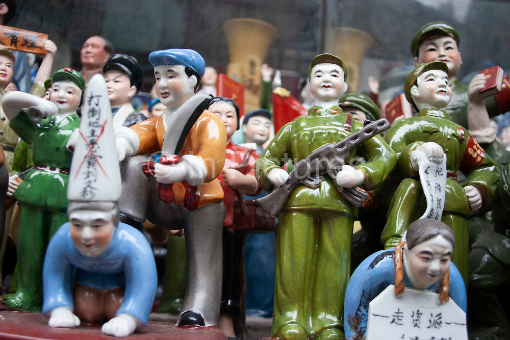Figures from the Cultural revolution for sale at a stall on Dong Tai Road, Dongtai Lu, street market in Shanghai, China. This small area, dedicated to antiques is lined with shops and the streets covered with stalls selling artifacts from Shanghais past. There are some genuine Chinese antiques which can be very expensive. But there are also a lot of fakes for sale too, like these figures. Usually snapped up by tourists who are under the impression they are getting a bargain.