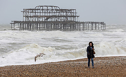 Licensed to London News Pictures. 21/05/2021. Brighton, UK. A walker braves the high winds on Brighton Beach as the Met Office issue weather warnings for high wind speeds and prolonged rain today. Rain and storm winds are expected today with wind speeds in excess of 55mph along the South Coast and London as the miserable May Spring weather continues. However, sun is on the way for the May Bank Holiday with temperatures expected to hit 22c by the end of the month. Photo credit: Alex Lentati/LNP