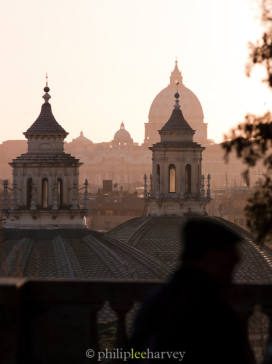 View of St. Peters Basilica and the domes of Santa Maria in Montesanto and Santa Maria dei Miracoli on Piazza del Popolo. Seen from the park at Villa Borghese, Rome, Italy.