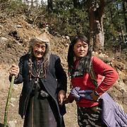 A grand daughter helping her grand mother on the trail. On the trek going from Laya village to the beginning of the drivable road.
