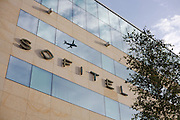 Reflected in the windows of hotel chain Sofitel, a climbing aircraft takes-off from Heathrow airport's Terminal 5.