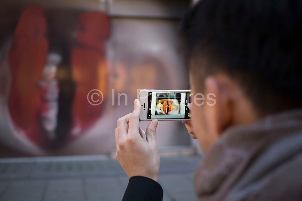 Taking a picture of large red lipstick covered lips hoarding on Bond Street, London, UK. Another of the exclusive shops in the area under refurbishment. The face, which is a close up of someone who has photocopied their features makes scale of passers by look small.