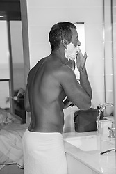 hot man putting shaving cream on his face after a shower