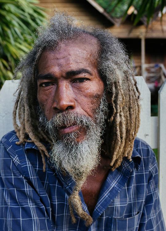 Local wood carver and beach Rastafarian, Frank Johnson, poses for a portrait. Roatan, Honduras.