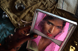 Radha Bhamwari, 15, observes herself in a cracked mirror the day before her wedding. Three young sisters Radha Bhamwari, 15, Gora Bhamwari, 13, and Rajni Bhamwari, 5, were married to their young grooms Aleen Mehra, Giniaj Mehra, and Kaushal Mehra, (ages to come), who were also siblings, on the Hindu holy day of Akshaya Tritiya, called Akha Teej in North India. Despite legislation forbidding child marriage in India (Child Marriage Restraint Act-1929) and the much more progressive Prohibition of Child Marriage Act (2006) and many initiatives to prevent child marriage, marrying children off at a very tender age continues to be accepted by large sections of society.