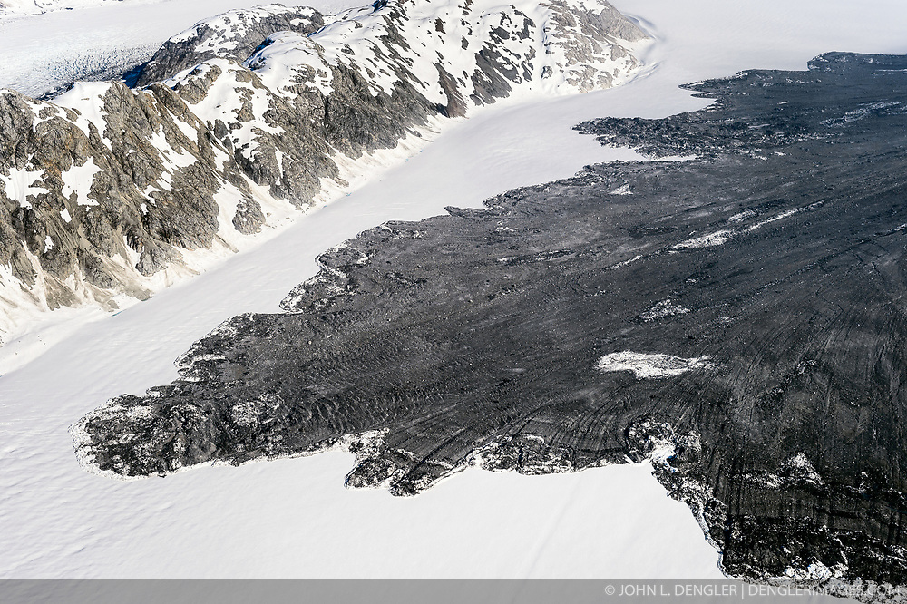 """A 4,000-foot-high mountainside released approximately 120 million metric tons of rock in 60 seconds during a landslide onto the Lamplugh Glacier in Glacier Bay National Park and Preserve. In an interview with the Alaska Dispatch News, geophysicist Colin Stark of Columbia University's Lamont-Doherty Earth Observatory, described the slide as """"exceptionally large."""" He compared the massive landslide to roughly 60 million medium SUVs tumbling down a mountainside.<br /> <br /> Mountainsides that were held strong by the heavy ice of glaciers become weak when the glaciers retreat. Erosion along with earthquakes are triggers that can cause the weakened slopes to collapse.<br /> <br /> The slide occurred on the morning of June 28  in a remote area of Glacier Bay National Park in southeast Alaska. It was first observed by Paul Swanstrom, pilot and owner of Haines-based Mountain Flying Service. Swanstrom noticed a huge cloud of dust over the Lamplugh Glacier during a flightseeing tour of Glacier Bay National Park several hours after the slide occurred. Swanstrom estimates the debris field to be 6.5 miles long, and one to two miles in width.<br /> <br /> This aerial photo of the Lamplugh Glacier landslide was taken two days after the landslide."""