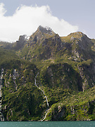 Waterfall pours into Milford Sound/Piopiotahi after a heavy rain; Fiordland National Park, New Zealand