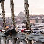 As a guesture of love that many tourists have adopted around the world, padlocks have been left on Galata Bridge in Istanbul. Spanning the Golden Horn and linking Eminonu with Karakoy, the Galata Bridge is a dual-level bridge that handles road, tram, and pedestrian traffic on the top level with restaurants and bars on the level below. In the distance is Suleymaniye Mosque.