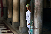 Muslim boy attends friday prayers.The muslim neighbourhood around the Nakhoda Mosque is a labyrinth of bazars and winding alleyways.
