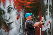Dale Grimshaw uses spray paint to create giant portraits in the woods - The 2016 Latitude Festival, Henham Park, Suffolk.