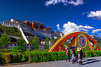 Tibetan pilgrims walk along Beijing Middle Road with the Potala Palace behind, Lhasa, Tibet (Xizang), China.
