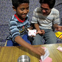 Asia, Nepal, Kathmandu. Two brothers playing a card game.