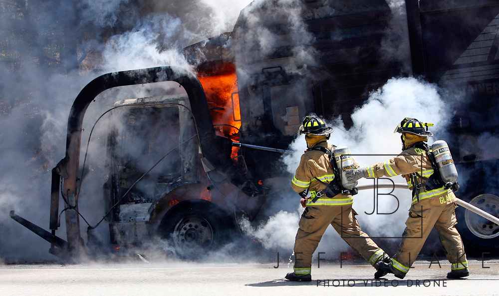 Columbia-Richland firemen attempt to put out an Allied Waste garbage truck engulfed in flames on the east-bound lane of I-20, two miles east of I-77.  Photo by Columbia, SC, photojournalist Jeff Blake