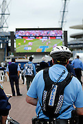 A policeman joins the crowd watching the 2008 Rugby League Grand Final on a big screen set up outside Olympic Stadium. Sydney, Australia
