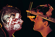 Application of virtual (artificial) reality computer systems in medical diagnostic imaging, showing a magnetic resonance image (MRI) of the head next to a scientist wearing a headset. Computer scientists here at the University of North Carolina aim to distill various types of diagnostic images, (X-rays, CT, MRI) into a vivid digital model, that is displayed through the head-mounted displays. Advantages of this type of presentation include not being bound by screen conventions, such as a lack of step back features, wider area views & the need to control a keyboard or mouse. Future uses may exist in the accurate targeting of radiotherapy. Stereo tactic radiotherapy technique. Model Released (1990)