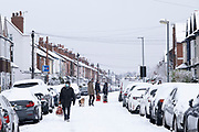 Local people wearing face masks in the snow due to the Covid-19 pandemic in Kings Heath on 24th January 2021 in Birmingham, United Kingdom. Deep snow arrived in the Midlands giving some light relief and fun during the current lockdown for people who simply enjoyed the weather.